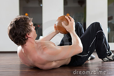 Man is exercising with medicine ball in gym