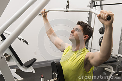 Man Exercising With Pulley In Gym