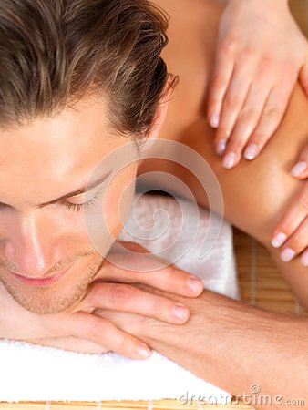 Man with eyes closed receiving shoulder massage