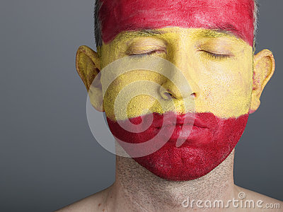 Man face painted flag Spain, closed eyes.