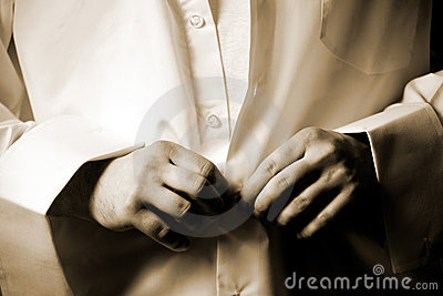 Man fastening buttons on white shirt