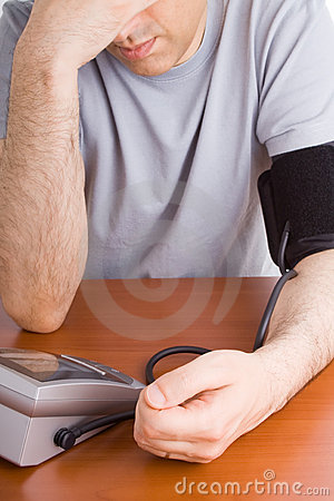 Man feeling sick and checking blood pressure