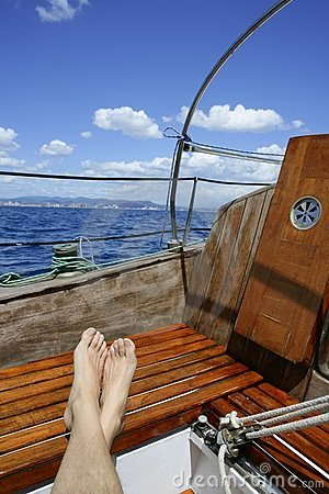 Man feet relax on golden wooden old sailboat