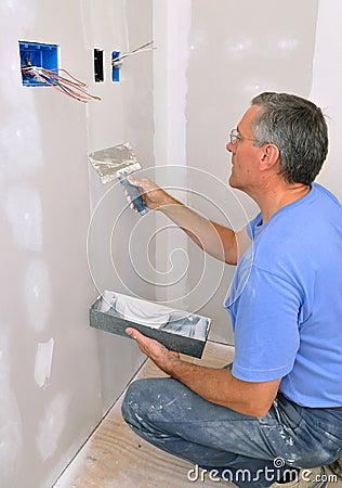 Man finishing drywall