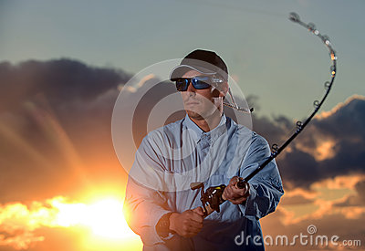 Man fishing with beautiful sunset in background