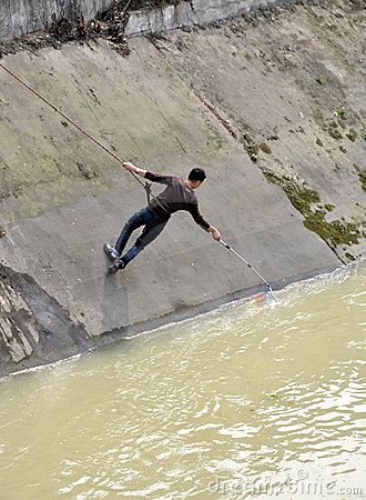 Man Fishing while Hanging from a Rope Editorial Photo