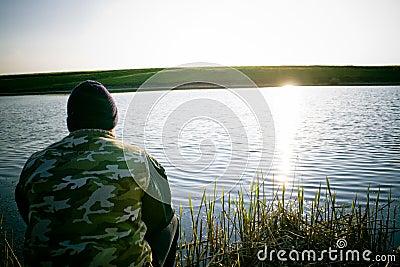 Man fishing on shore of lake