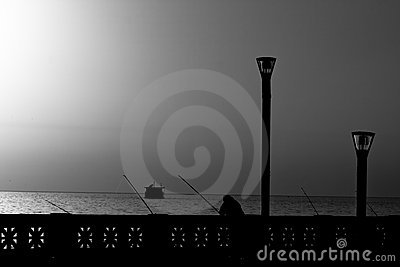 Man fishing at sunrise in B/W