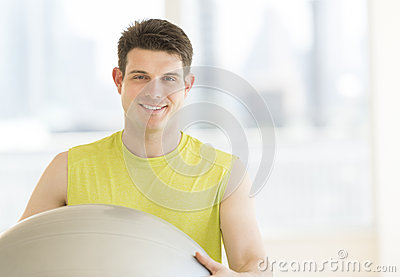 Man With Fitness Ball Smiling In Gym