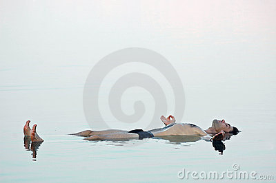 Man floating in a glassy water of dead sea
