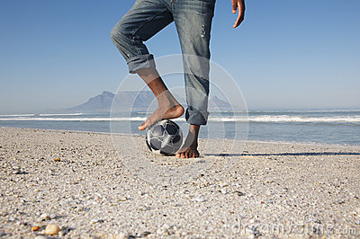 Man With Foot On Soccer Ball At Beach