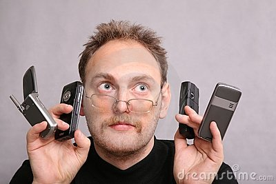 Man with four cell phones