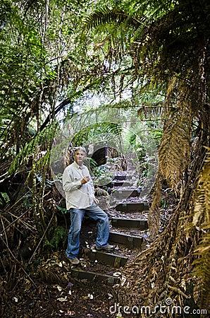 Man framed by ferns, Tasmanian rainforest