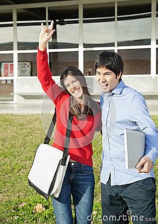Man With Friend Gesturing Devil Horns On College