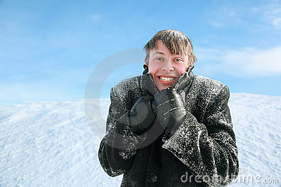Man froze and hides head in collar of overcoat