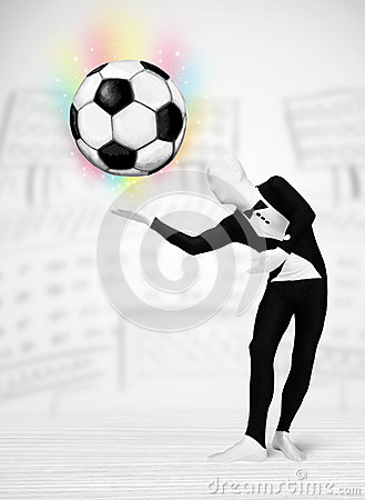Man in full body suit holdig soccer ball Stock Photo