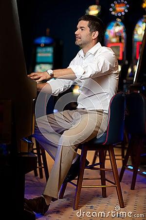 Man gambling at slot machine