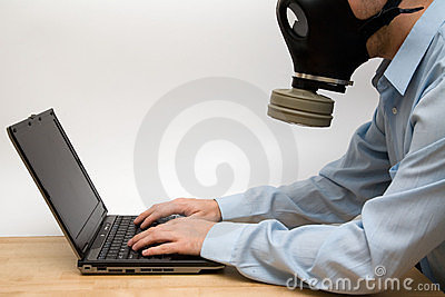 Man in gas mask and a  laptop