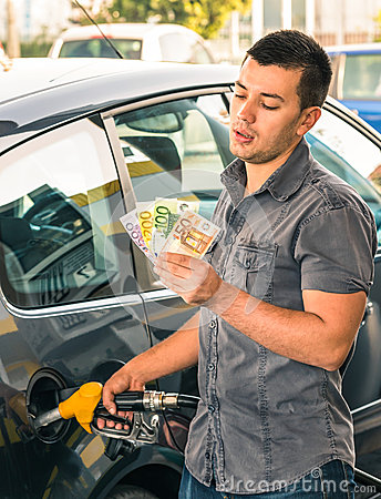 Man at gasoline station dealing with money for rising prices