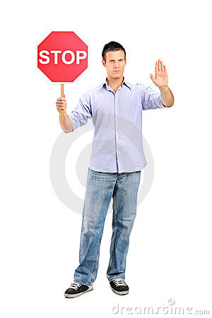 Man gesturing and holding a traffic sign stop