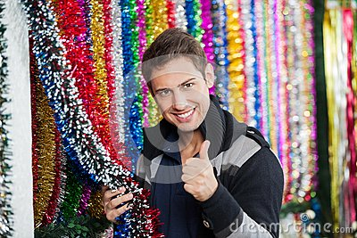 Man Gesturing Thumbs Up While Holding Tinsels At