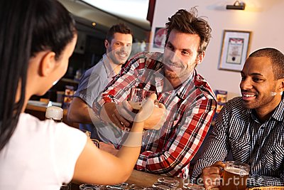 Man getting glass of beer from bartender