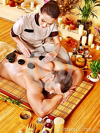 Man getting stone therapy massage .