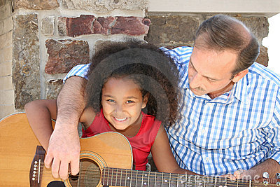 Man and girl playing guitar