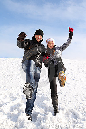 Man and girl stand on snowy area and put leg up