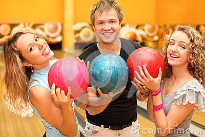 Man and girls made row of balls in bowling club