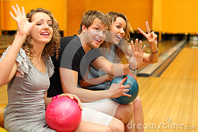 Man and girls sit, hold balls  in bowling club