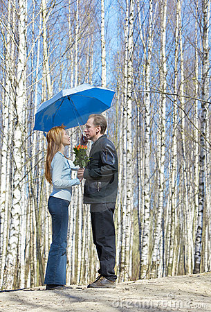 Man gives girl bouquet under umbrella
