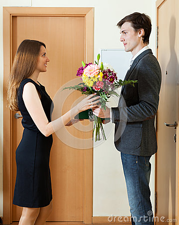 Man giving flowers and gift to woman