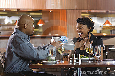 Man Giving Gift to Woman at Restaurant