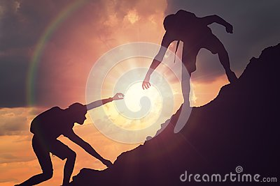 Man is giving helping hand. Silhouettes of people climbing on mountain at sunset Stock Photo