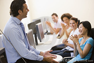 Man giving lecture in applauding computer class