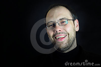 Man with glasses and beard laughing in black