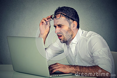 Man with glasses having eyesight problems confused with laptop software Stock Photo