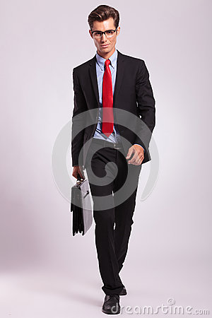 Man with glasses walking with briefcase