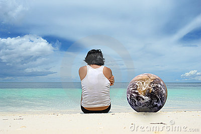 Man with globe sitting on beach