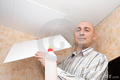 Man glues ceiling tile
