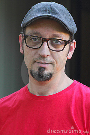 Man with goatee, flat cap and glasses