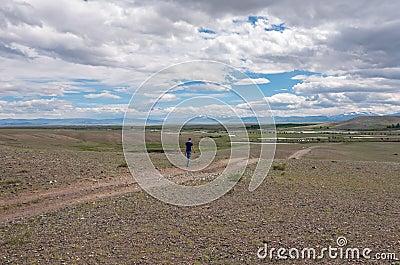man goes along dirt road steppe sky