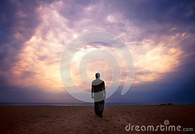 Man goes to the sea  under cloudy sky