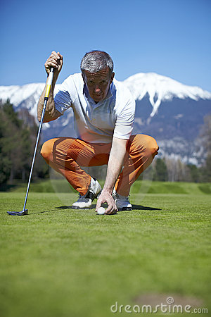 Man golfer putting his golf ball on the green