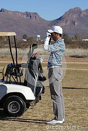 Man Golfing Using Rangefinder