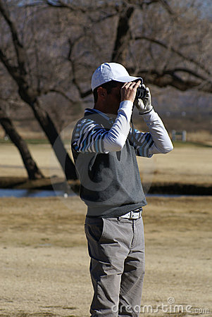 Man Golfing Using Rangefinder