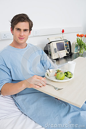 Man in gown having mean in hospital