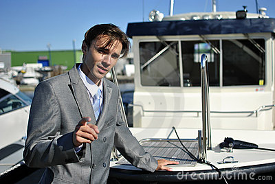 Man in a gray business suit near the yacht