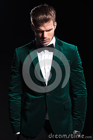 Man in a green velvet suit is looking down
